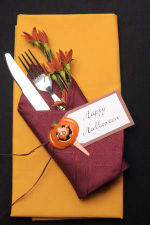 Happy Halloween table place setting with red and orange napkins on a black tablecloth, and halloween decorations  photo