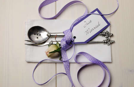 Pretty purple polka dot wedding table place setting on white shabby chic table with Just Married tag  photo
