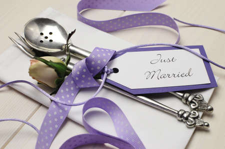 Pretty purple polka dot wedding table place setting on white shabby chic table with Just Married tag  Close up  Stock Photo