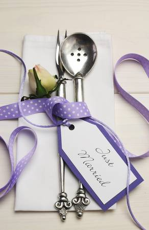 Pretty purple polka dot wedding table place setting on white shabby chic table with Just Married tag  Vertical  photo