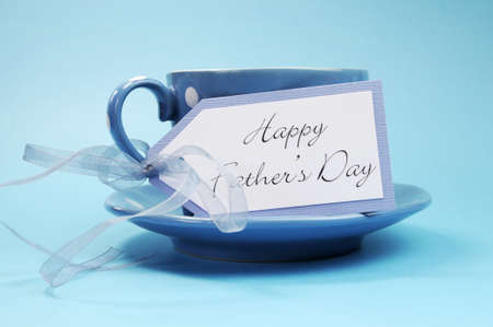 Happy Fathers Day gift tag with a cup of coffee or tea for Dad in a blue polka dot cup and saucer against a blue background  photo