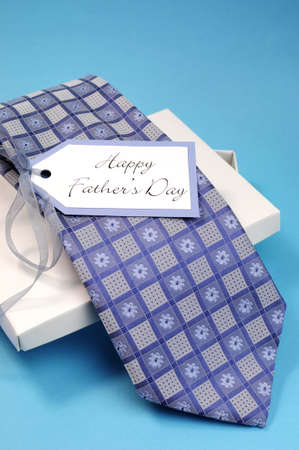 Happy Fathers Day gift of a blue pattern check tie in a white gift box present with gift tag against a blue background  Vertical  photo