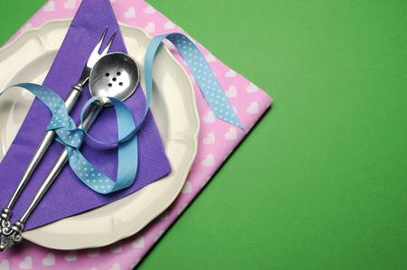 space for copy: Pretty color dinner or lunch table place setting in green, purple and pink for birthday, modern Christmas, Easter, wedding, Valentine, or Mothers Day, with copy space for your text here.