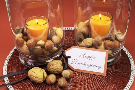centerpiece: Beautiful Happy Thanksgiving table setting centerpiece with ornage candle and nuts in decorative glass hurrican lamp vase and autumn arrangement