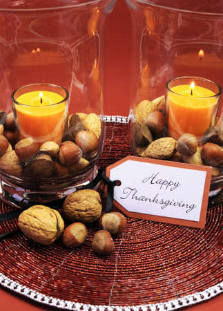 centerpiece: Beautiful Happy Thanksgiving table setting centerpiece with ornage candle and nuts in decorative glass hurrican lamp vase and autumn arrangement Vertical  Stock Photo