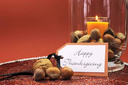 thanksgiving: Beautiful Happy Thanksgiving table setting centerpiece with orange candle and nuts in decorative glass hurricane lamp vase and autumn arrangement Stock Photo