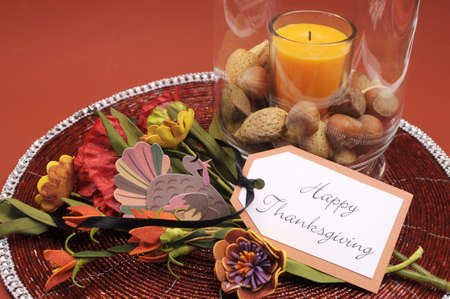 centerpiece: Beautiful Happy Thanksgiving table setting centerpiece with orange candle and nuts in decorative glass hurricane lamp vase and autumn arrangement with turkey decoration