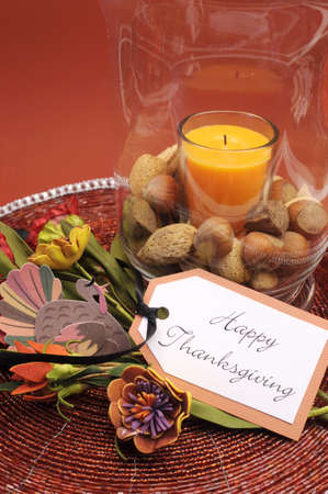 Beautiful Happy Thanksgiving table setting centerpiece with orange candle and nuts in decorative glass hurricane lamp vase and autumn arrangement Vertical with turkey decoration  Stock Photo