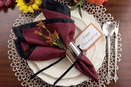 Beautiful Thanksgiving table setting with lace doily place setting and fine bone china with vintage silverware, red and black napkins on dark mahogany wood table with autumn pumpkin, grapes and sunflower decorations
