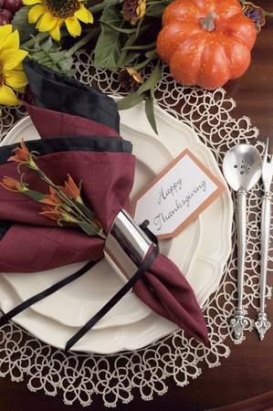 Beautiful Thanksgiving table setting with lace doily place setting and fine bone china with vintage silverware, red and black napkins on dark mahogany wood table with autumn pumpkin, grapes and sunflower decorations  Vertical  photo