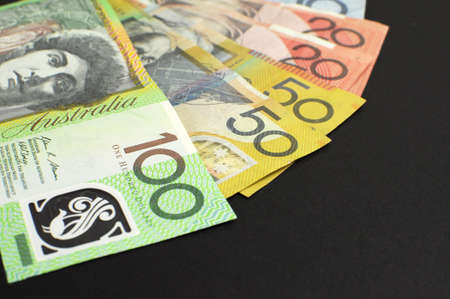 australian money: Australian paper money, including one hundred, twenty, ten, five and fifty dollar notes against a black background, with copy space