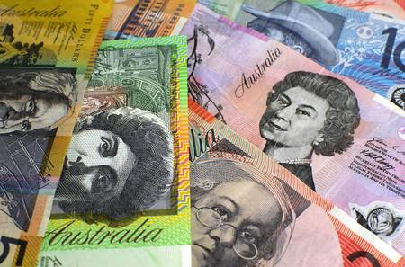 five dollars: Australian paper money, including one hundred, twenty, ten, five and fifty dollar notes against a black background