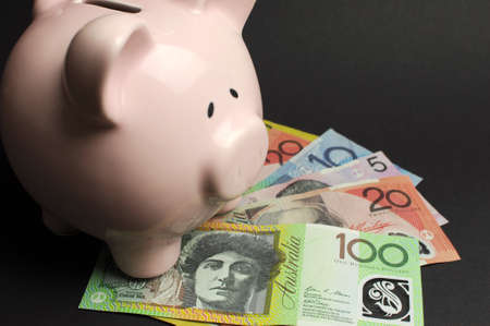 five dollars: Pink Piggy Bank with Australian money against a black background, for savings concept