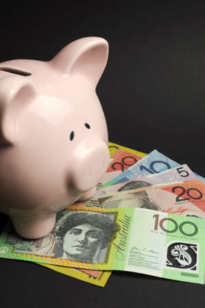 Pink Piggy Bank with Australian money against a black background, for savings concept  Vertical  photo