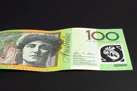 thrifty: Australian green and gold  100 hundred dollar note, against a black background, laying flat  Stock Photo