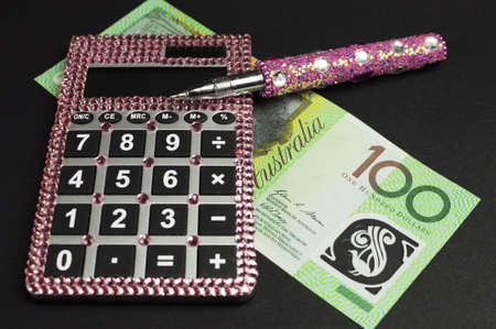 Savings and money management concept with Australian dollar notes, pink calculator against a black background  photo