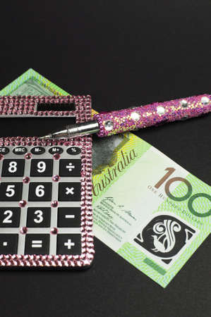 Savings and money management concept with Australian dollar notes, pink calculator against a black background  Vertical  photo