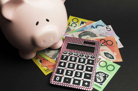 five dollars: Savings and money management concept with Australian dollar notes, pink calculator and piggy bank against a black background  Stock Photo