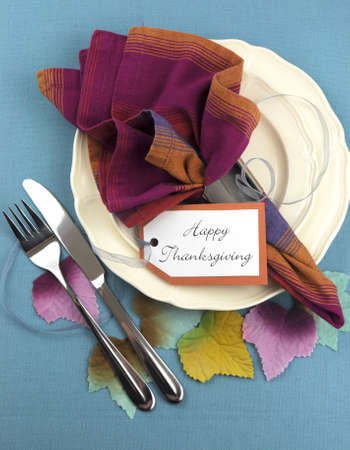thursday: Modern Thanksgiving dining table place setting on aqua blue tablecloth, with material autumn leaves, in pink blue and orange theme. Vertical aerial view.