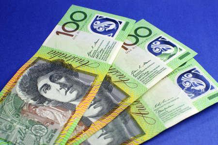australian money: Three hundred Australian green and yellow notes on blue background.