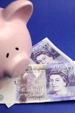 Two English Bank of England Twenty Pound notes on blue background with pink piggy bank Vertical. photo