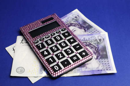 Two English Bank of England Twenty Pound notes on blue background, with pink bling calculator. photo