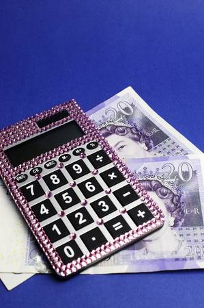 Two English Bank of England Twenty Pound notes on blue background, with pink bling calculator. Vertical. photo