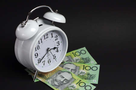 White old fashion alarm clock with Australian hundred dollar notes on black background photo