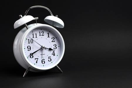 Beautiful white old fashion alarm clock against black background photo