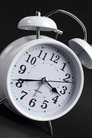 Beautiful white old fashion alarm clock against black background  Close up angle  photo