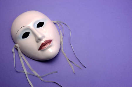 Pale pink ceramic mask on purple background for acting, performance or theatre concept. Horizontal with copy space for your text here. photo