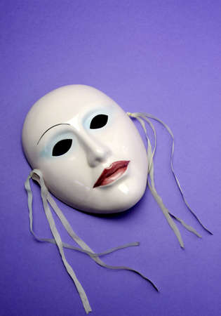 thespian: Pale pink ceramic mask on purple background for acting, performance or theatre concept. Vertical with copy space. Stock Photo