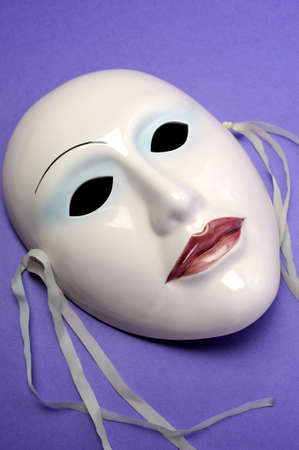 Pale pink ceramic mask on purple background for acting, performance or theatre concept. Close up. photo