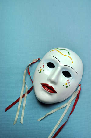 Pale blue ceramic mask on aqua blue background for actor, performance or theatre concept. Vertical with copy space. photo