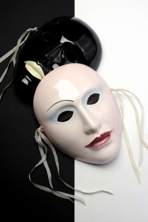 Black and white theme ceramic masks for actor, performance, emotions and theatre concept. Vertical. photo