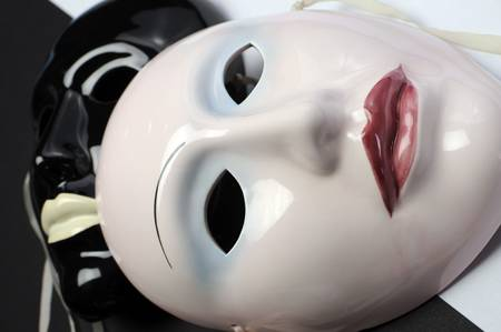 comedy tragedy: Black and white theme ceramic masks for actor, performance, emotions and theatre concept. Close up on flesh colored mask. Stock Photo