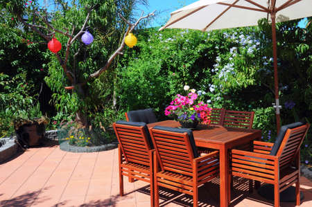 entertaining area: Beautiful and lush courtyard garden with wooden table and chairs, and white market umbrella in summertime. Close up on entertaining area. Stock Photo