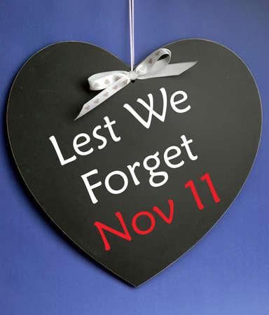 remembrance day poppy: Lest We Forget message written on heart shape blackboard for Remembrance Day on November 11. Stock Photo