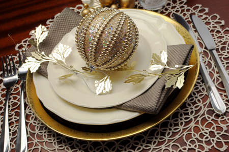 Latest trend of gold metallic theme Christmas  formal dinner table place setting with fine bone china, bauble and festive decorations  Close up  photo