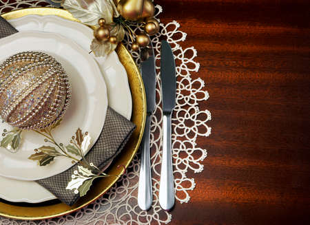 Latest trend of gold metallic theme Christmas  formal dinner table place setting with fine bone china, bauble and festive decorations, with copy space for your text here  photo
