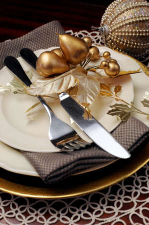 Latest trend of gold metallic theme Christmas  formal dinner table place setting with fine bone china, bauble and festive decorations  Close up on cutlery and plates photo