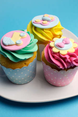 Beautiful pink, aqua blue and yellow cupcakes on white heart shape plate, for baby shower or childrens party. photo