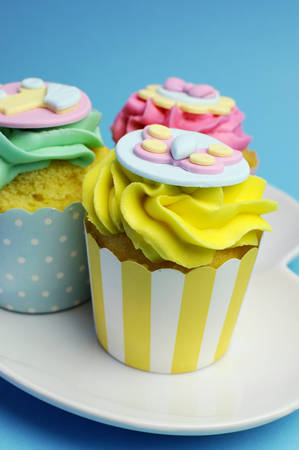 topper: Beautiful pink, aqua blue and yellow cupcakes on white heart shape plate, for baby shower or childrens party.
