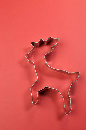 Merry Christmas reindeer and festive shape cookie cutters on red background with copy space for your text here, for colorful holiday food and kitchen backgrounds photo