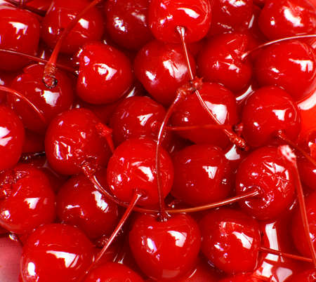 Festive background of red cocktail maraschino cherries with stems Stock Photo