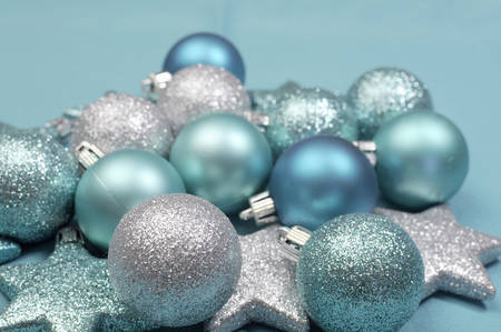 Festive background of aqua torquiose pale blue christmas glitter baubles and stars on a pale aqua blue material tablecloth background. Close up with selective focus. photo