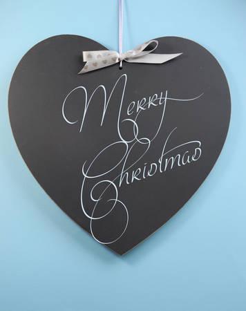 Aqua blue theme Merry Christmas message greeting written on heart shape blackboard. photo
