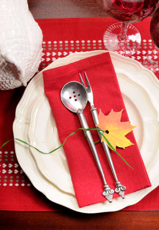 Red and white theme festive fine dining table setting with autumn fall leaf decoration, crystal wine glass, and turkey tureen pot, for Thanksgiving or Christmas place setting. Stock Photo - 23831781