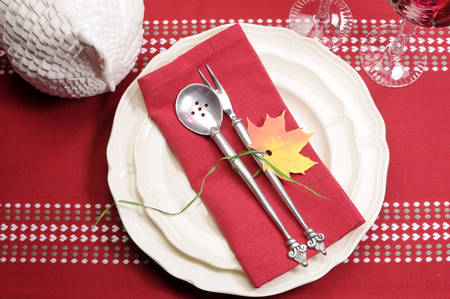 Red and white theme festive fine dining table setting with autumn fall leaf decoration, crystal wine glass, and turkey tureen pot, for Thanksgiving or Christmas place setting. Stock Photo - 23831785