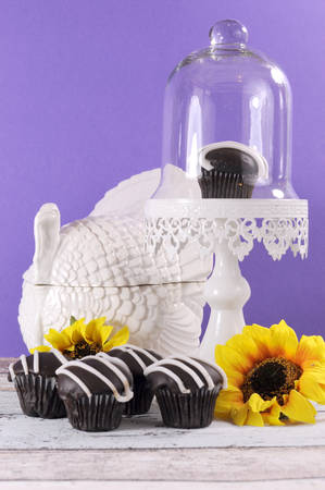 Autumn Thanksgiving theme chocolate cupcakes with turkey tureen and sunflowers on shabby chic table against a purple wall. photo